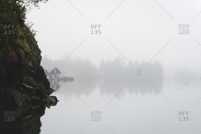 Scenic view of calm lake during foggy weather