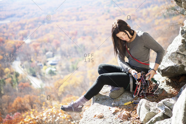 Woman looking at climbing equipment while sitting on rock