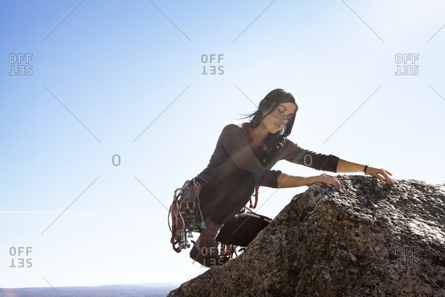 Woman rock climbing against sky on sunny day