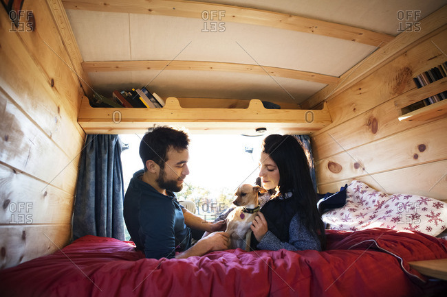 Couple looking at dog while relaxing on bed in camper van