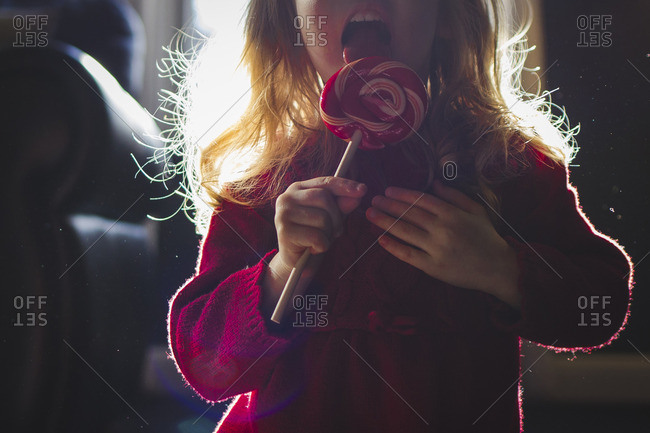Midsection of girl eating lollipop at home