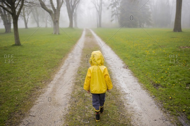 Rear view of boy in raincoat walking on dirt road during foggy weather
