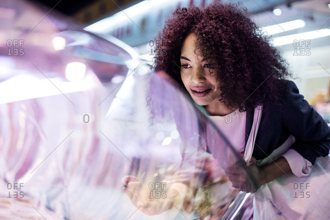 Woman looking at display cabinet while shopping in market