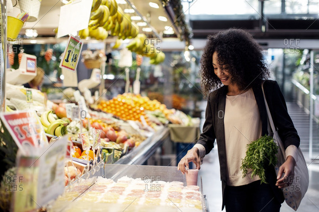 Woman buying juice while standing at store
