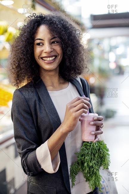 Woman enjoying juice while standing in supermarket
