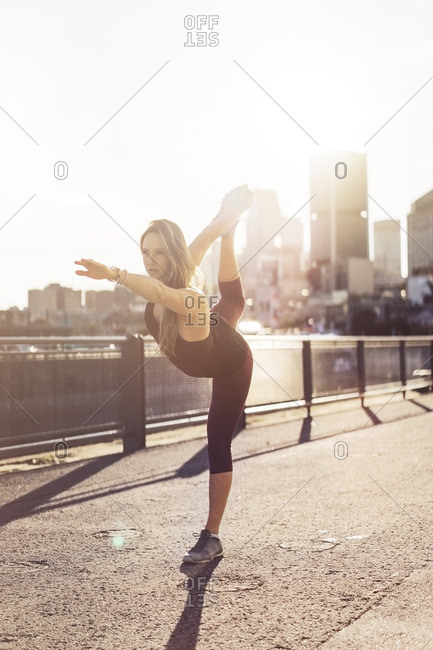 Woman practicing yoga in city during sunrise