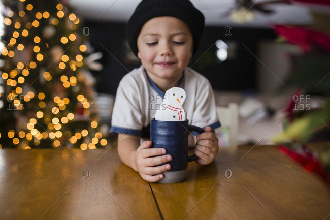 Cute boy holding cup with marshmallow snowman at table in home