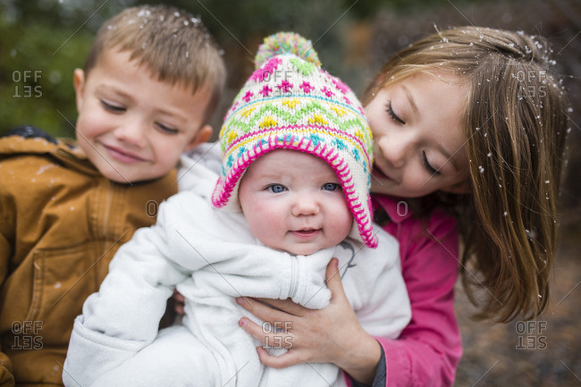 Portrait of cute baby girl with siblings at backyard