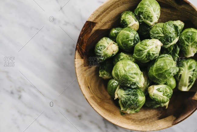 Overhead view of Brussels sprouts in wooden bowl