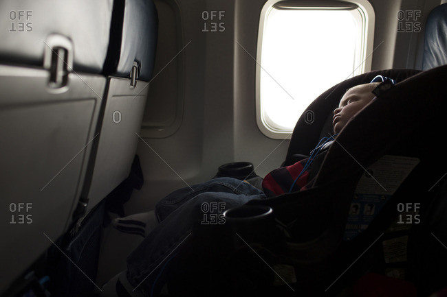 Boy with headphones sleeping while traveling in airplane