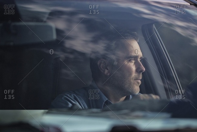 Man looking away while sitting in car seen through windshield
