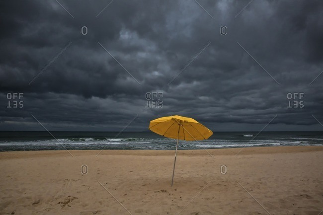 Beach umbrella on sand by sea against storm clouds