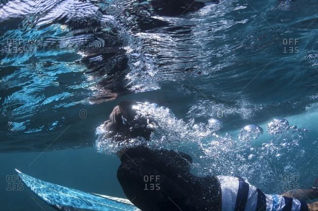Side view of man surfing undersea