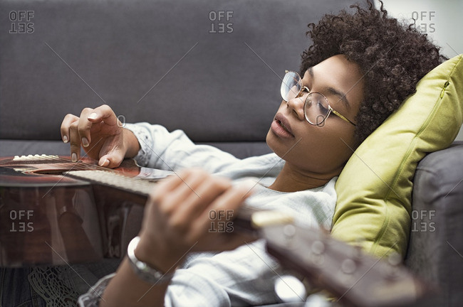 Woman playing acoustic guitar while lying on sofa at home