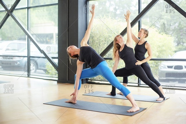 Woman practicing yoga while instructor assisting friend at studio