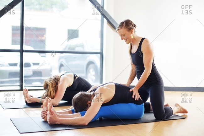 Woman practicing seated forward bend pose while instructor assisting friend at studio