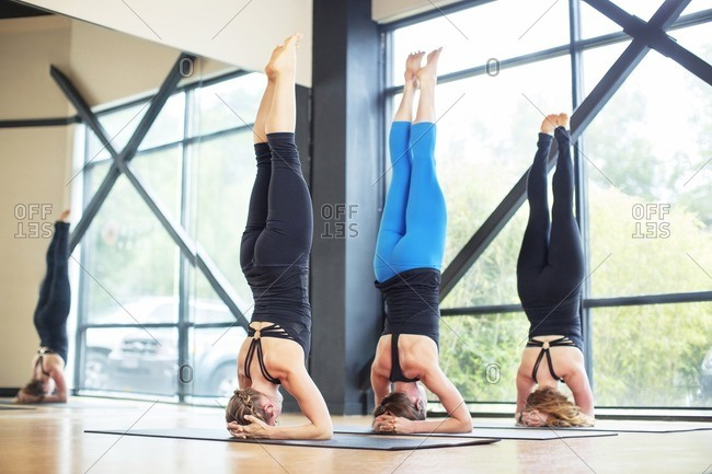 Friends practicing headstand pose in yoga class