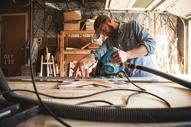 Serious craftsperson using circular saw on wooden plank at workshop