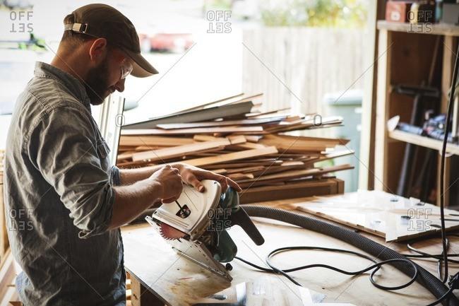 Craftsperson checking circular saw while working in workshop