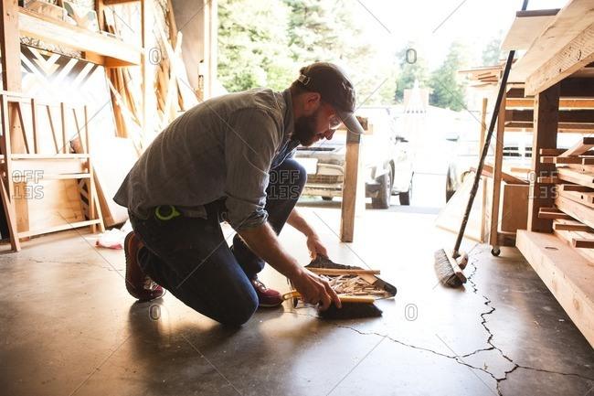 Full length of craftsperson cleaning wooden shavings on floor at workshop