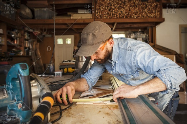Serious craftsperson measuring wooden art at workshop