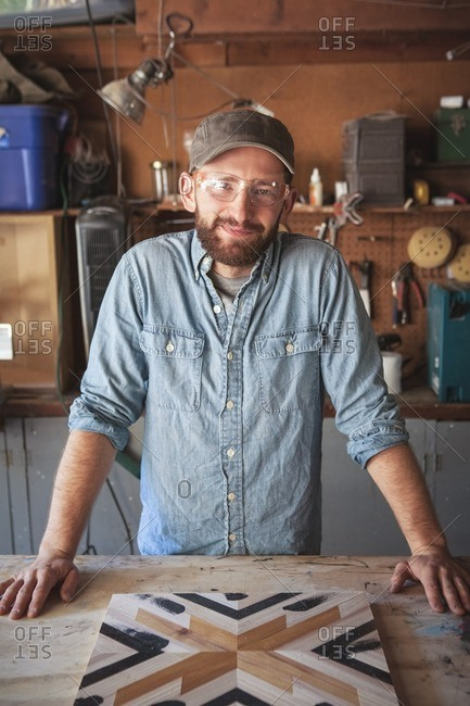 Portrait of smiling craftsperson with wooden art at workbench