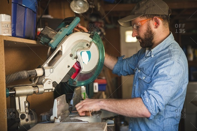 Side view of craftsperson using circular saw over wooden planks at workshop