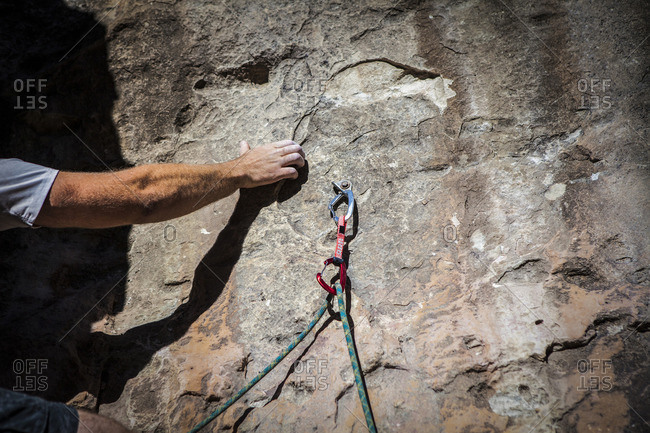 Cropped image of hand gripping while rock climbing