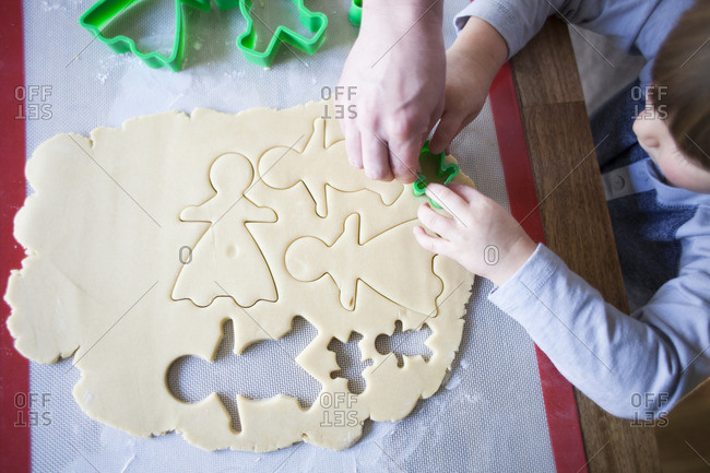 Overhead view of woman and son cutting dough with pastry cutters in kitchen