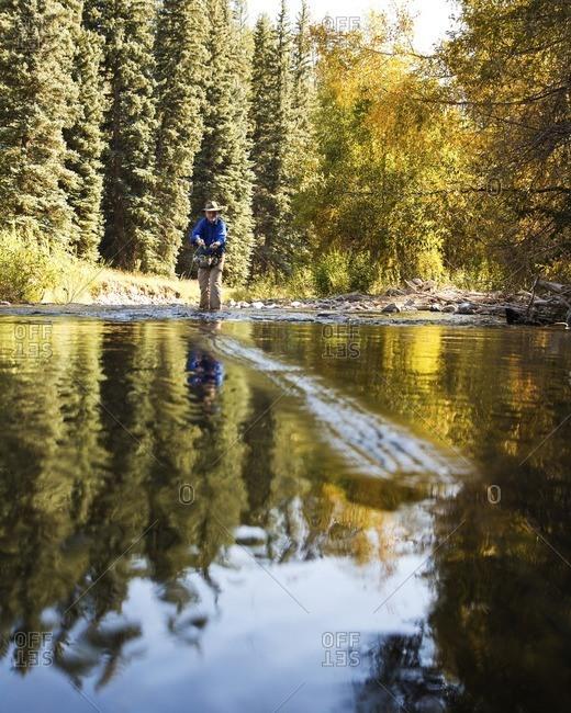 Man wearing hat fishing in stream