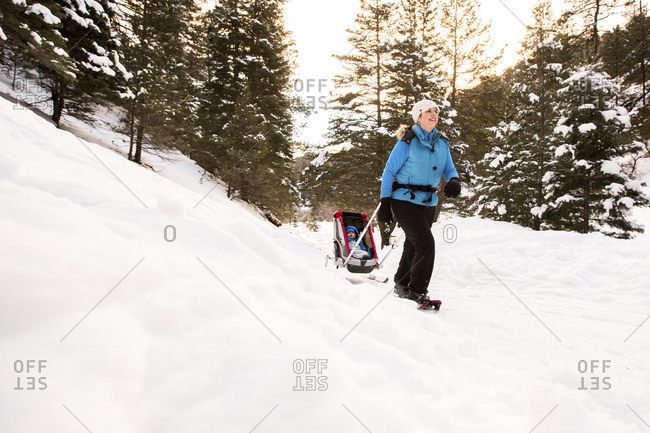 Woman with son in sled on snowy field against trees