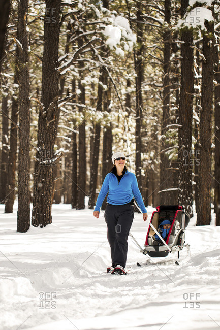 Happy woman with son in sled walking on snowy field