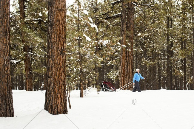 Woman with son in sled walking on snowy field