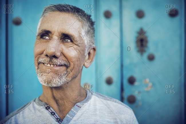 Close-up of thoughtful man against blue wall
