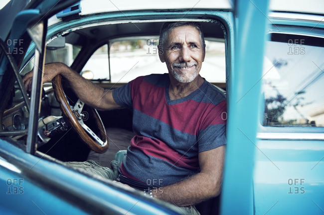 Man looking away while sitting in vintage car