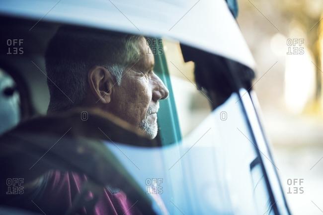 Thoughtful man sitting in car seen through windshield