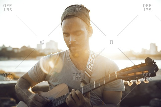 Man playing guitar while sitting at lakeshore against clear sky