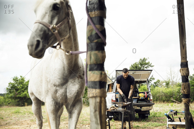 Farrier making horseshoe while standing on field by pick-up truck