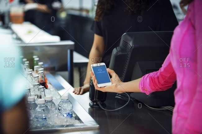 Cropped image of woman scanning smart phone while paying bill in restaurant