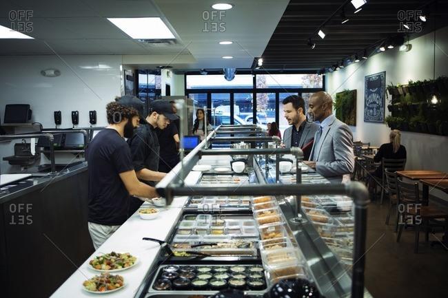 Happy business people ordering food in restaurant