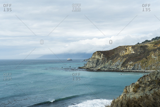 Scenic view of sea by mountains against cloudy sky