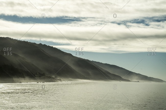 Scenic view of sea by mountains against cloudy sky during foggy weather