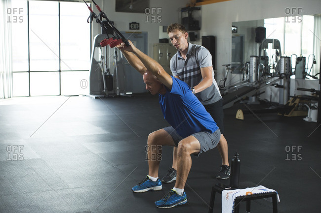 Trainer assisting man for practicing stretching exercise with resistance band in gym