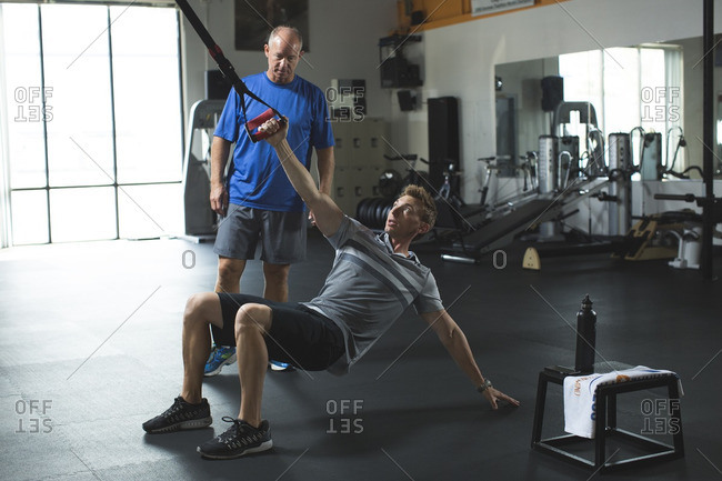 Trainer showing stretching exercise with resistance band to customer in gym