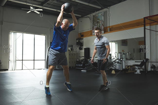 Trainer looking at customer exercising with fitness ball in gym