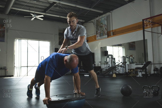 Trainer assisting customer while practicing push-ups on bosu ball with balance disc in gym