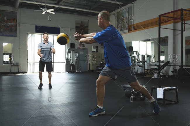 Customer passing fitness ball to trainer while exercising in gym