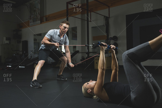 Trainer assisting woman for practicing stretching exercise with resistance band in gym