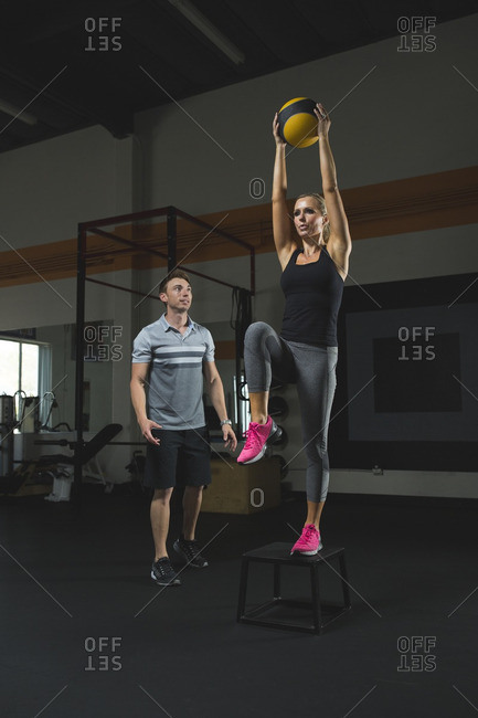 Trainer looking at woman holding fitness ball standing on stool in gym