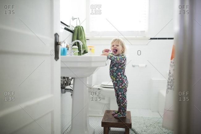 Portrait of baby girl brushing teeth while standing on stool in bathroom
